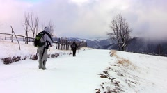 Tourists with backpack, go behind down a snow covered road in the forest Stock Footage