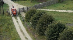 Tractor with trailer climbing a dirt road bordered by large green bushes Stock Footage