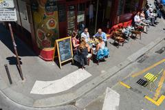 parisians and tourists enjoy food and drinks in cafe - stock photo