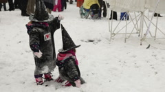 Two children dressed up as witches play in the snow during an Ethnics carnival - stock footage