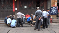Classic Chinese scene, men play chess in backstreets of old town Stock Footage