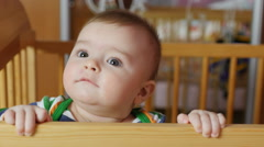 Baby boy 5-6 months trying to stand in a babycot. Close the frame. Stock Footage