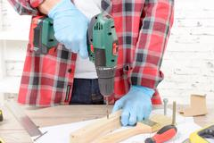 Carpenter drilling hole in plank, in his workshop Stock Photos
