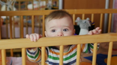 Baby boy 5-6 months trying to stand in a babycot. Stock Footage