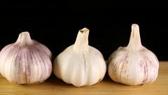 Garlic on wood chopping board. Stock Footage