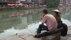 Two Chinese men are fishing in a small stream in Fenghuang Stock Footage
