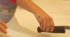 Kid's Hands Girl is Putting Stamps on Paper Sheet in Art Gallery People Paint Stock Footage