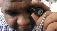 Jeweler examining diamond thoroughly through loupe Stock Footage