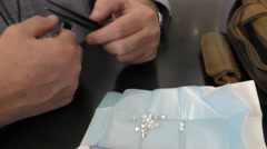 A trader inspects perfectly shaped brilliant diamonds Stock Footage