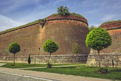 Medieval fortified walls and ornamental trees Stock Photos