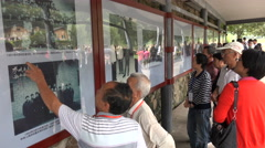 Tourists look at pictures of Mao Zedong's youth in Shaoshan, his birthplace - stock footage