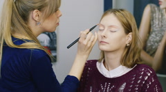 Young woman doing her makeup in the salon - stock footage