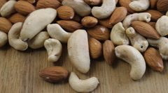 Close up shot of a pile of nuts rotating on wooden table Stock Footage