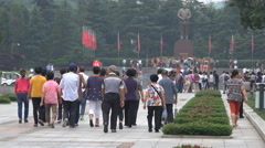 Chinese visitors walk to Mao Zedong statue in his hometown Shaoshan Stock Footage