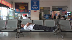Funny sign above sleeping man in Chinese bus station, silence please, no noise - stock footage