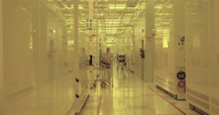Workers in clean suits in a semiconductors manufacturing facility - stock footage