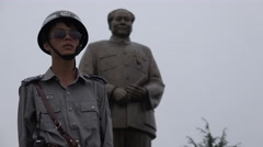 Police officer stands guard at Mao Zedong statue in Shaoshan, central China Stock Footage