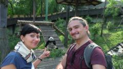 Two happy people looking at panda in the zoo Stock Footage
