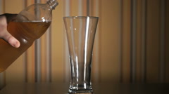 Beer is poured from bottle into a beer  high glass Stock Footage