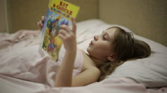 The girl is reading the book bedtime - stock footage