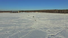 Aerial, group fishermen on the frozen lake in winter - stock footage