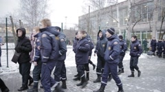 Many young men in emercom uniform walk in training field. Snow. Day Stock Footage