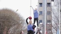 Cheerleaders in jackets make acrobatic elements on stage. Red shakers. Outdoor Stock Footage