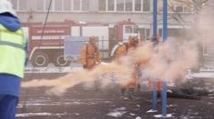 Men in orange protect suits, respiratory masks save man. Emercom practice. Spray - stock footage