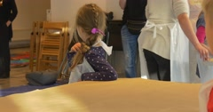 Kid Girl is Sitting at the Table Looking Around Family Master Class in Art Stock Footage