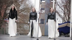 Lady in maxi white skirts, leather jackets sing and dance on stage on street Stock Footage