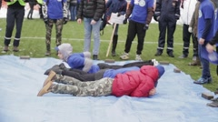 Young boys lie on blue tarpaulin, stand on command. Emercom training. Audience Stock Footage