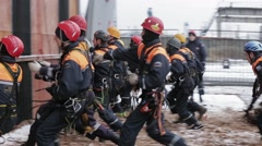 Men in rescue uniform run to training wall, attach carbine with rope. Emercom - stock footage