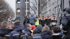 Woman and man hang gold medals on young boys in rescue uniform on street stage Stock Footage
