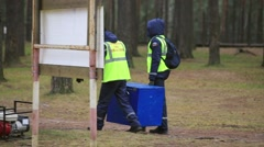 Two men in rescue uniform hold big blue box in forest. Emercom camping - stock footage