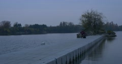 Man Holds a Laptop Freelancer on a Pier River Small Island Overgrown With Trees Stock Footage