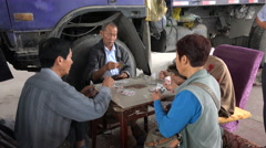 Chinese people play cards on old tables, next to a truck Stock Footage