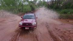 Aerial drone filming of Toyota 4Runner crossing red mud river Stock Footage