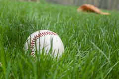 Baseball in Grass with Glove behind Stock Photos