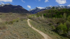 Aerial drone filming of jogger and mountain biker on Rocky Mountain trail Stock Footage