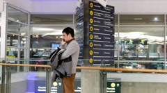 Man making a phone call with pilots passing through inside YVR Airport. Stock Footage