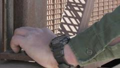 Border Patrol Agent Closes Gate of Fence Between US and Mexico - stock footage