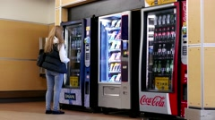 Close up woman buying a bottle of water at vending machine inside YVR airport - stock footage