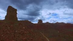 Aerial drone filming of tall desert structures with dramatic cloudy sky Stock Footage