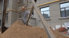 Chinese construction worker using shovel at building site in Hohhot Stock Footage