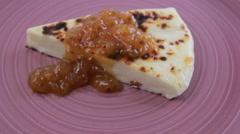 Finnish squeaky cheese with cloudberry jam on a purple plate Stock Footage
