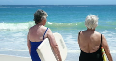 Senior woman holding surfboard - stock footage