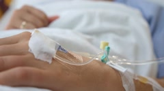 Female Patient with IV Drip Needle Lying on Bed in Hospital Stock Footage