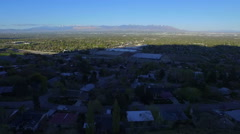 Aerial drone filming of valley, houses, freeway and mountains in distance Stock Footage