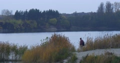 Man Stands For a While Near Lake River Sandy Bank Landscape Tourist Walks Away Stock Footage