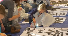Families Paint Together at Master Class Kids Writing on a Big Sheets of Paper Stock Footage